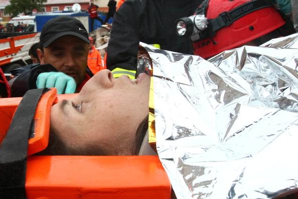 Турецкие спасатели несут Сэмиху Карадуман, мать двухнедельной девочки Азры Карадуман. Эриш, 25 октября 2011 года. Фото: Adem Altan/Getty Images