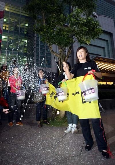 Депутат г.Тайбэй Ли Вэньинь (справа) со своими единомышленниками разбрасывали солёный рис, изгоняя нечистую силу напротив здания, в котором Чень Юньлинь присутствует на банкете. Фото: ЦАН