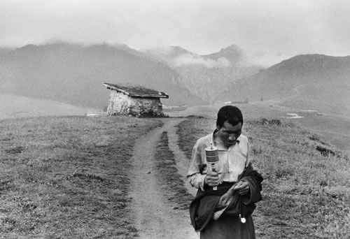 Тибетец, наклонив голову, идёт по дороге в горной долине. Провинция Ганьсу. 2000 год. Фото: Lu Ning