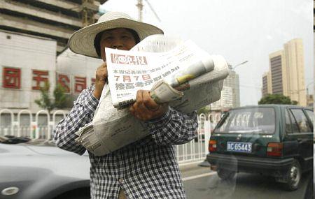 Женщина продающая газеты на улицах Пекина. Фото: PETER PARKS/AFP/Getty Images