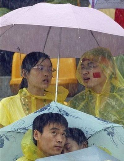 Глядачі під зливою чекають результатів змагань із стрільби з лука серед жінок, 10 серпня 2008 р. у Пекіні. Фото: AFP