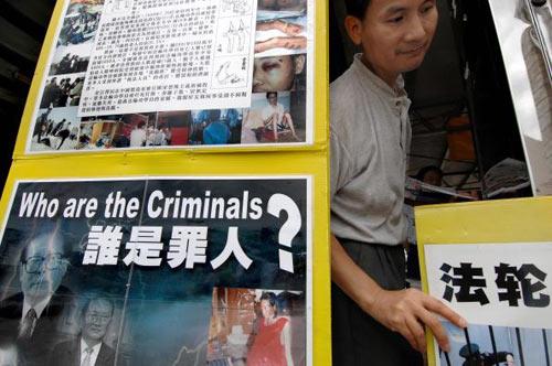 Послідовники Фалуньгун проводять акцію протесту з плакатами. Фото: TED Aljibe/afp/getty Images