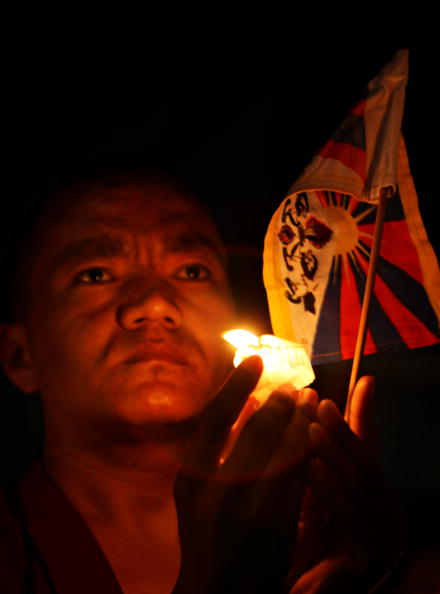 Тибетцы участвуют в мирной акции со свечами, чтобы выразить свою боль и страдания, причиненные политикой компартии Китая, в пригороде Непала, Тибет. Фото: PRAKASH MATHEMA/AFP/Getty Images