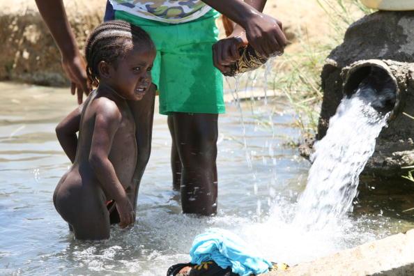 Девочка плачет в то время когда ее мать стирает белье в воде из водосточной трубы. Ангола, 15 км к северо-западу от Бенгелы, 22 января 2010. Фото Халеда Десоки /AFP/Getty Images