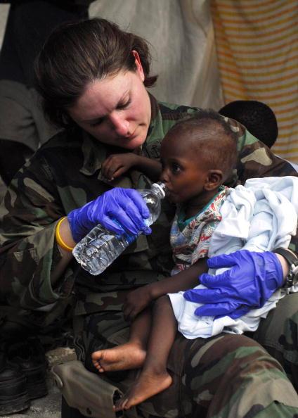 Медперсонал десантного корабля ВМС США Картер-Хол дает воду обезвоженному ребенку. Деревня Бонел, Гаити. На фото - старшина 1-го класса Моника Хилей. Фото: ВМС США/ Getty Images