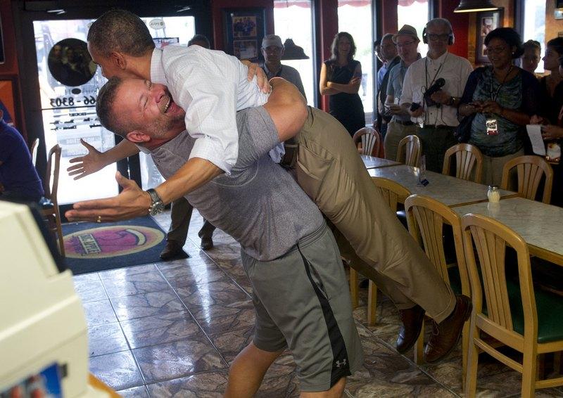 Форт-Пирс, США, 9 сентября. Барак Обама попал в объятия хозяина пиццерии Скотта Ван Дазера во время 2-х дневной поездки по штату Флорида. Фото: SAUL LOEB/AFP/GettyImages