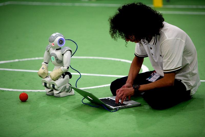 Тегеран, Иран, 5 апреля. Студент из лаборатории изучения механотроники диагностирует робота перед началом футбольного матча между машинами на открытом чемпионате роботов. Фото: BEHROUZ MEHRI/AFP/Getty Images