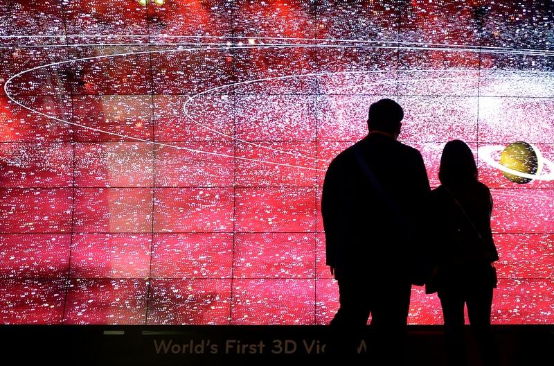 Лас-Вегас, США, 8 января. Посетители выставки электроники CES-2013 любуются первой в мире 3-D стеной, созданной фирмой LG. Фото: JOE KLAMAR/AFP/Getty Images