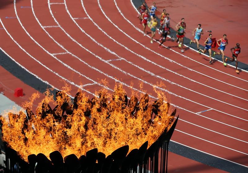 Лондон, Англия, 3 августа. Олимпийские игры 2012. Легкоатлеты бегут по дорожке мимо олимпийского огня. Фото: Streeter Lecka/Getty Images