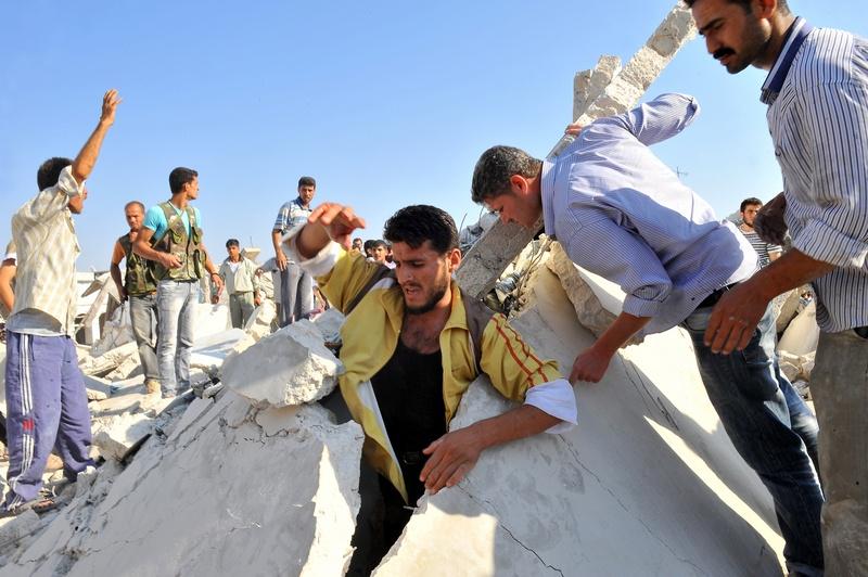 Азаз, Сирия, 15 августа. Спасатели ищут людей под развалинами города после удара авиации. Фото: BULENT KILIC/AFP/GettyImages