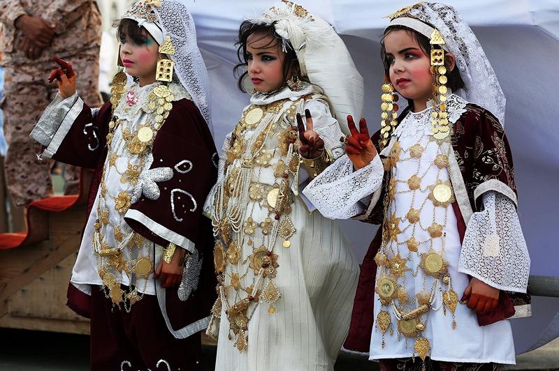 Триполи, Ливия, 1 апреля. Девочки в традиционных костюмах знаком «V» (победа) встречают факел свободы и развития, открывающий 2-ю ливийскую международную ярмарку. Фото: MAHMUD TURKIA/AFP/Getty Images
