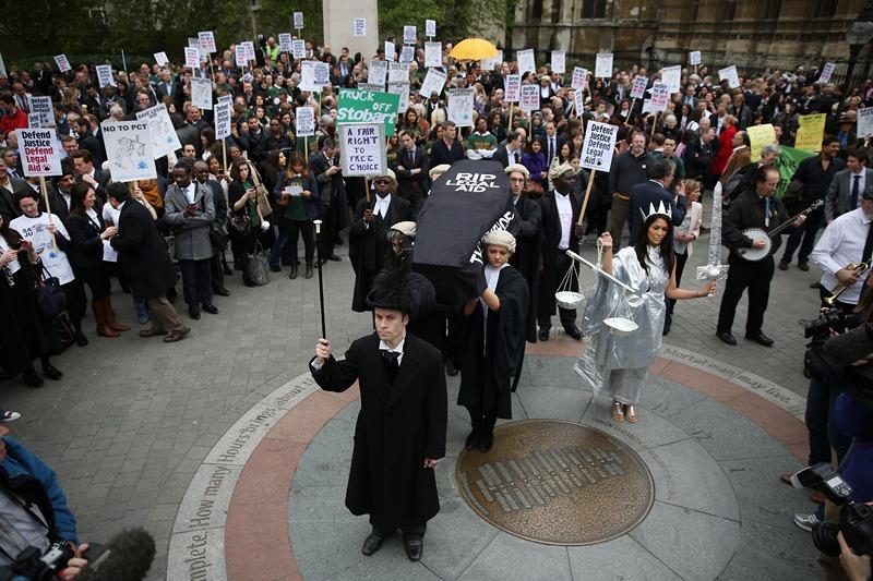 Лондон, Англия, 22 мая. Демонстранты несут гроб как символ смерти правовой помощи гражданам, призывая правительство отменить запланированные сокращения в сфере юридической помощи. Фото: Peter Macdiarmid/Getty Images