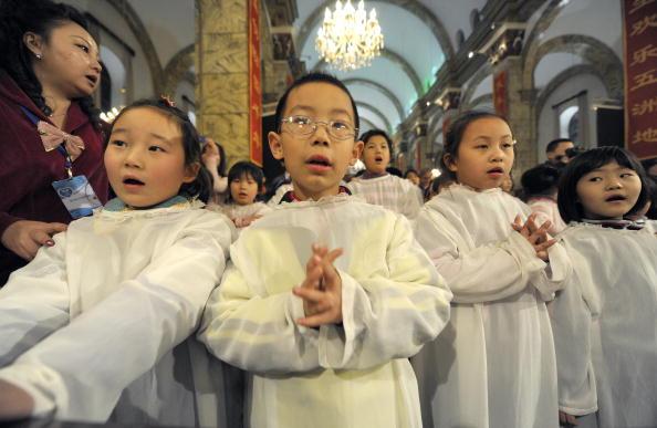 Дети молятся в канун рождественских праздников. Китай. Фото: LIU JIN/AFP/Getty Images