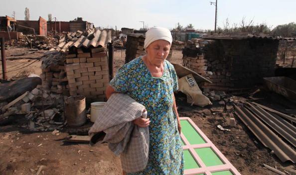 Женщина уходит от своего сгоревшего дома на окраине Воронежа 31 июля 2010 года. Фото: Alexey SAZONOV/AFP/Getty Images