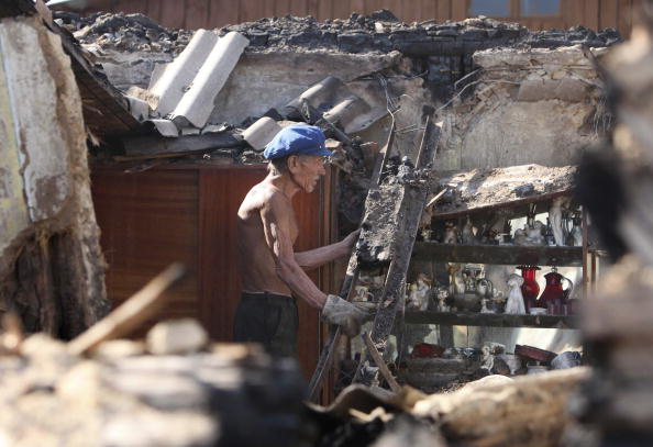 Мужчина зашел в свой сгоревший дом в Воронеже 1 августа 2010 года. Фото: Alexey SAZONOV/AFP/Getty Images