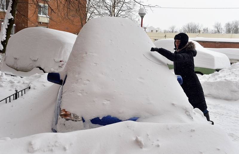 Киев, Украина, 23 марта. Девушка пытается откопать машину после сильнейшего снегопада. Фото: SERGEI SUPINSKY/AFP/Getty Images