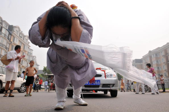 Китаянка Чжан Тинтин протянула на своей косе 6 автомобилей. Фото: AFP/Getty Images