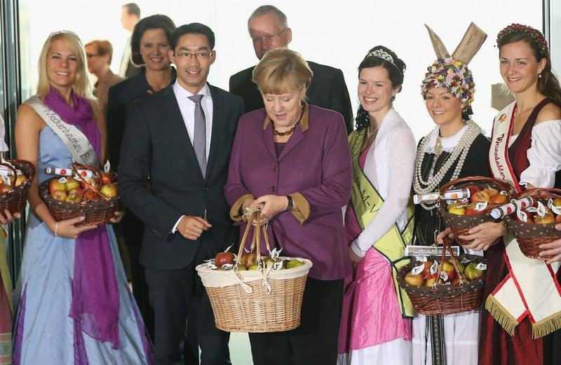 Берлин, Германия, 17 октября. Шесть «королев урожая» из яблочных регионов страны вручили Ангеле Меркель корзины с ароматными яблоками. Фото: Sean Gallup/Getty Images
