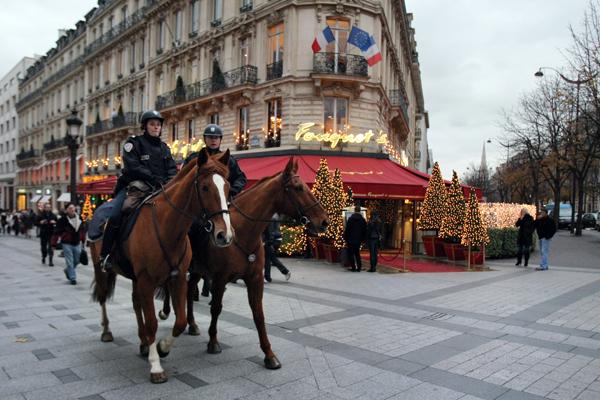 Более чем за три неделе до рождественских праздников полицейские на лошадях патрулируют известную улицу Champs-Elysees в Париже. Фото: PIERRE VERDY/AFP/Getty Images