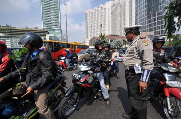 Индонезийский полицейский на проезжей части Джакарты раздает автомобилистам деревья в рамках экологической кампании, посвященной предстоящему саммиту ООН по проблемам климата в Копенгагене. Фото: ADEK BERRY/AFP/Getty Images