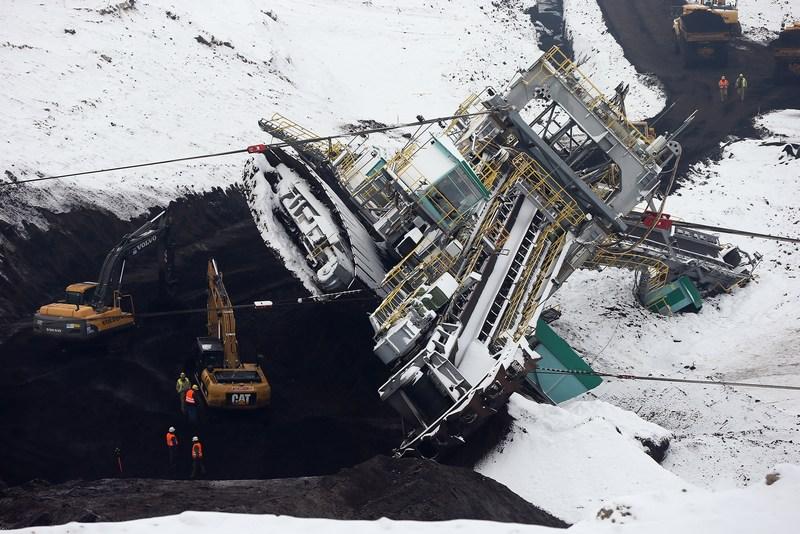 Дойцен, Германия, 25 января. Рабочие пытаются вытащить 950-тонный экскаватор, провалившийся в трещину на открытом угольном карьере. Фото: Sean Gallup/Getty Images
