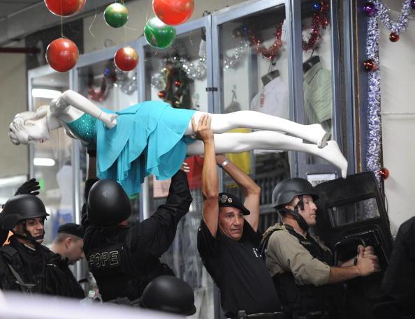 Полицейские, прикрываясь манекеном, пытаются войти в здание, где преступник взял в заложники 64 летнюю кореянку. 3 декабря, Асунсьон, Парагваи. Фото:NORBERTO DUARTE/AFP/Getty Images