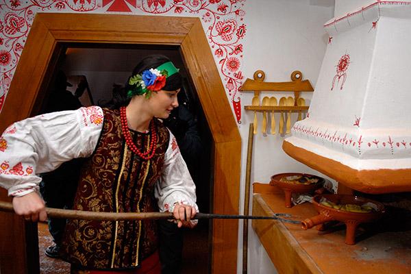 Девушка засовывает в печь пряники приготовленные детьми. Фото: Владимир Бородин/The Epoch Times