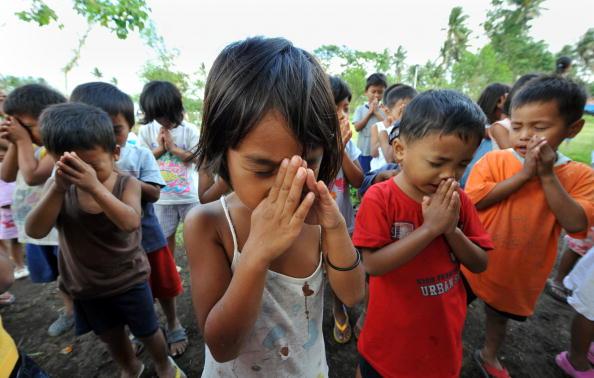 Дети молятся во во временном приюте. Они были эвакуированы из своих домов, расположенных у подножья вулкана Майон на Филиппинах. Местные эксперты сообщают, что извержение вулкана может произойти в любой момент в течение ближайших двух недель. Фото: TED AL