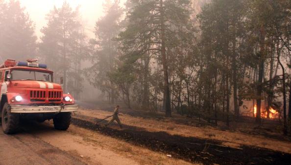 Пожарник бежит к пламени в поселке Белоомут, находящемся в 130 км от Москвы. Фото: ANDREY SMIRNOV/AFP/Getty Images
