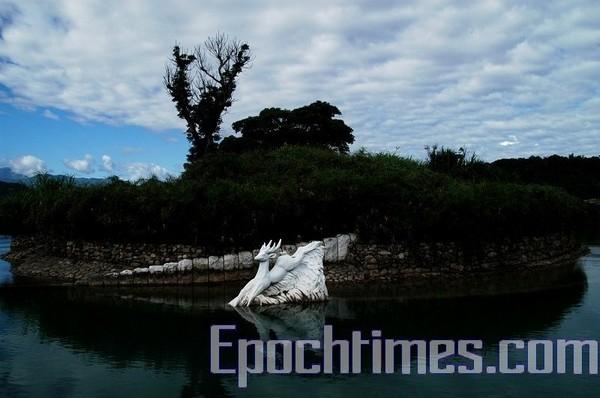 Статуя белого оленя, прыгающего в озеро. Фото: The Epoch Times