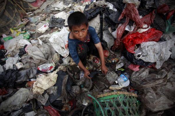 На крупнейшей свалке в Джакарте после школы работает восьмилетний мальчик, помогая своим родителям продавать найденные вещи. Индонезия 26 января 2010. Фото Юлет Ифансасти/ Getty Images
