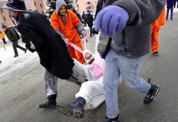 Демонстранты несут активиста, переодетого в костюм кролика, во время митинга против ежегодного Всемирного экономического форума (WEF). 30 января 2010 г. Фото: FABRICE COFFRINI/AFP/Getty Images