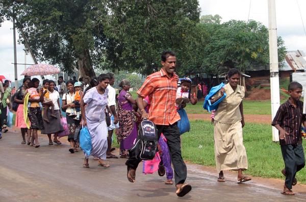 Лишенные крова по причине войны жители Шри-Ланки, схватив свои мелкие вещи, покидают лагерь для задержанных в местности Вавуния. Тысячи людей были помещены в государственный лагерь на время этнического конфликта на острове. Он прекратился 1 декабря. Фото: