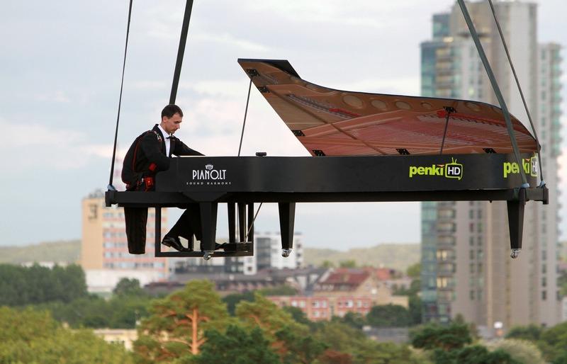 Вильнюс, Литва, 10 августа. Маэстро музицирует, в то время как его вместе с инструментом поднимают на воздушном шаре во время музыкального фестиваля Piano.lt. Фото: PETRAS MALUKAS/AFP/GettyImages