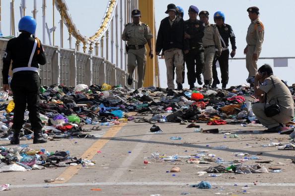 Полицейские осматривают место давки, обувь и другой мусор, 24 ноября 2010 года. Сотни скорбящих камбоджийских семей вышли 24-25 ноября на траурную церемонию по погибшим родным, а также выразить свой гнев по поводу неорганизованной безопасности на мероприя