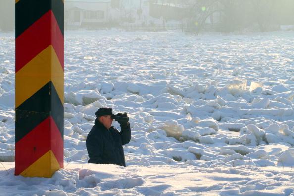 Человек наблюдает ледяной покров на реке Одер около Шведта, где за эту зиму замерзло 14 бездомных. Восточная Германия. 26 января 2010. Фото Майкл Урбан/ AFP/Getty Images