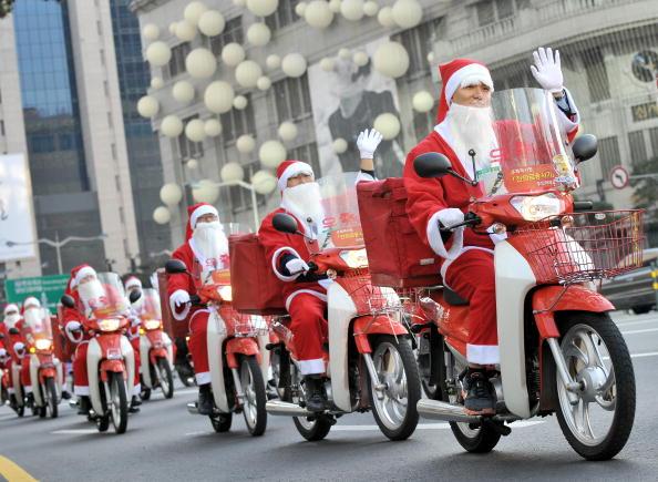 Почтальоны, одетые в костюмы Санта-Клаусов, развозят подарки бедным людям в рамках благотворительной кампании. Сеул, Южная Корея. Фото: JUNG YEON-JE/AFP/Getty Images