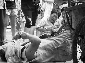 От жары умер дворник. Руки его так и остались в положении, когда он отдыхал, облокотившись на руль. Город Кайфэн провинции Хэнань. Фото с epochtimes.com