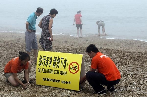 Активисты организации «Гринпис» на берегу Жёлтого моря устанавливают табличку с предупреждением о том, что купаться там нельзя из-за загрязнения нефтью. Фото: AFP