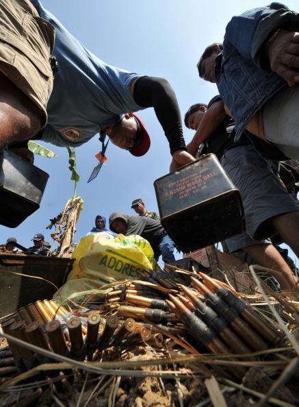 Полицейские собирают выкопанные боеприпасы и оруже в поместье, принадлежащем губернатору Магунданао. Чиновника подозревают в организации массовой бойни на шоссе, во время которой боевики застрелили и изрубили мачете 57 человек, многие из которых были жу