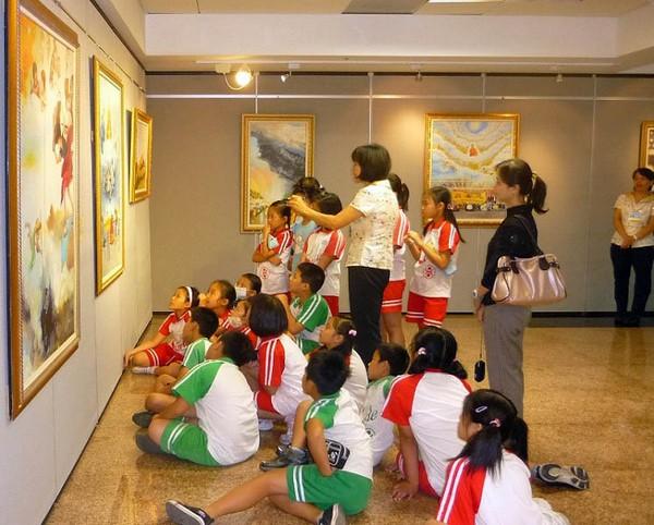 Учителя и ученики начальной школы Сюдэ рассматривают картины