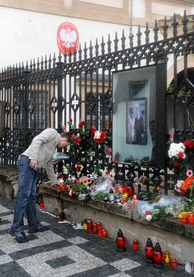 Человек зажигает свечу перед польским посольством 10 апреля 2010 в Праге. Фото:MICHAL CIZEK/AFP/Getty Images