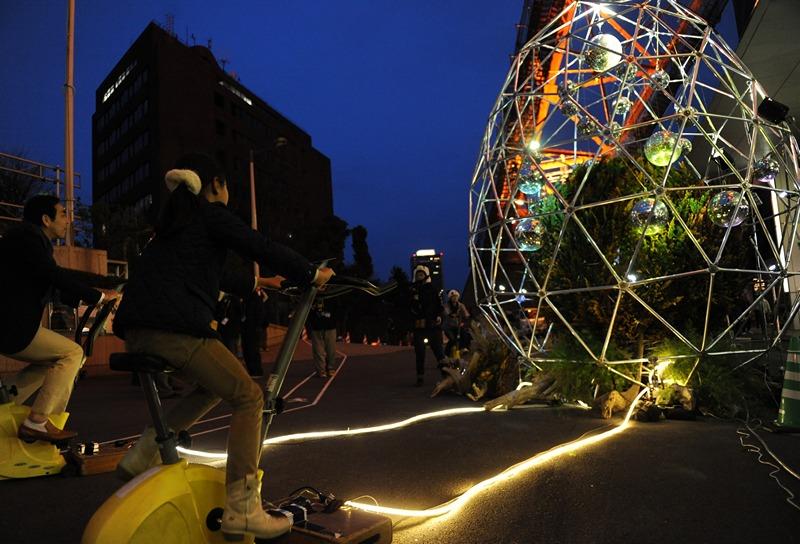 Токио, Япония, 23 марта. Два горожанина вырабатывают электричество для освещения зеркального шара внутри арт-инсталляции во время 7-й кампании «Час Земли», проводимую для снижения энергозатрат. Фото: RIE ISHII/AFP/Getty Images