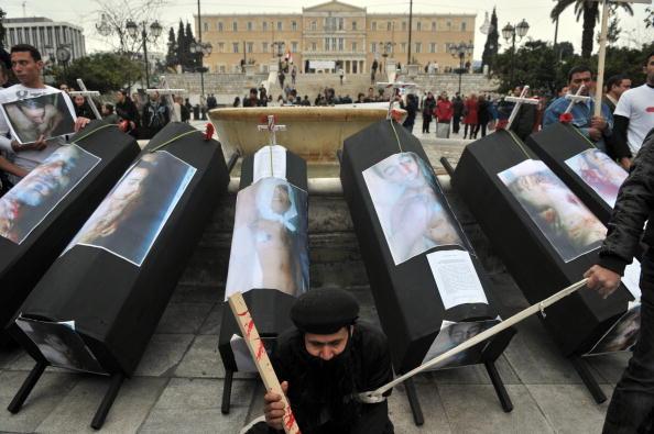 Египетские христиане в знак протеста против убийства своих единоверцев в Нага-Хаммади в Египте демонстрирует макеты гробов и фотографии убитых. Афины, 21 января 2010. Фото: Лоуиса Гоулиамаки/ AFP / Getty Images)