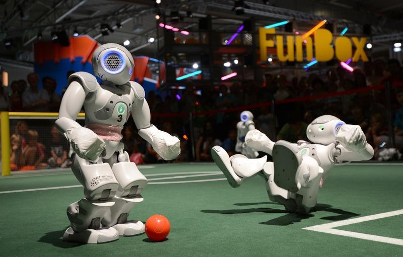 Эссен, Германия, 13 августа. Роботы играют в футбол на ярмарке, призванной пробудить интерес к исследованиям и творчеству среди детей и юношества. Фото: PATRIK STOLLARZ/AFP/GettyImages