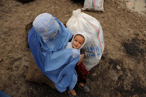 Бездомная афганская женщина ожидает транспорта после того, как получила продовольствие во время раздачи его бедным в Кабуле, столице Афганистана. Фото: SHAH MARAI/AFP/Getty Images