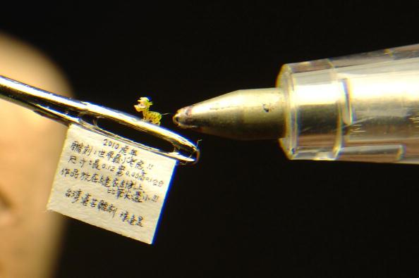 Тайваньский мастер миниатюрных изделий Чэнь Фонг-Шеан изготовил крохотного тигра размером с миллиметр, которого можно поместить в ушко иголки. Провинция Тайбэй, Тайвань, 18 января 2010. Фото: Patrick Lin / AFP / Getty Images