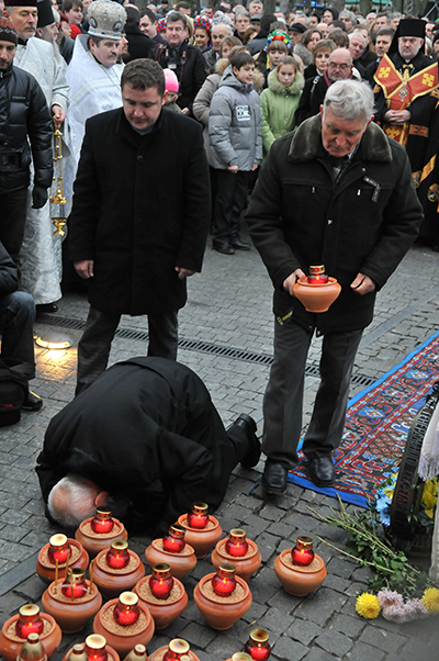 Мужчина поставил свечку и встал на колени на мемориальныех мероприятиях ко Дню памяти жертв Голодомора в Киеве 27 ноября 2010 года. Фото: Владимир Бородин/The Epoch Times Украина