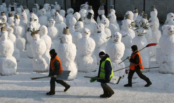 Дворники проходят мимо снеговиков в Москве. Ффото: Getty-Images-News