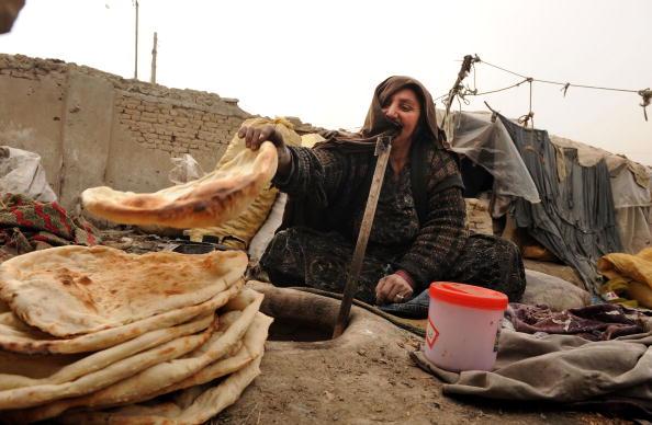 Женщина печет хлеб в лагере для беженцев в Кабуле. Афганистан. Фото: SHAH MARAI/AFP/Getty Images